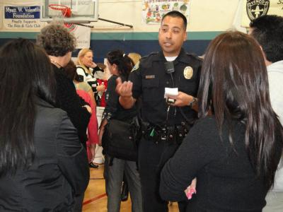 A police officer in uniform talking to a couple people at a community event