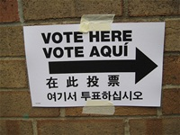 Sign saying vote here in four languages