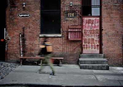 A person walking in Brooklyn, New York in front of a brick building