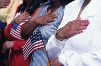 People's right hands over their hearts holding the American flag.