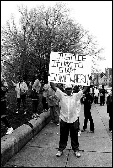 "Person holding a sign that says ""Justice, it has to start somewhere!"""