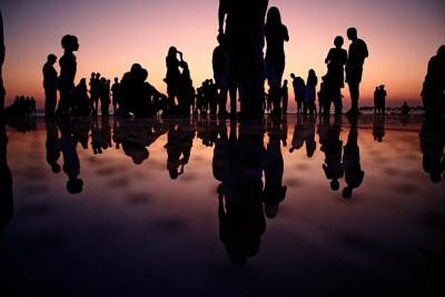 Shadows of people standing near a sunset with a reflection