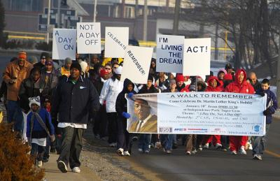 A group of people walking with signs to honor Dr. Martin Luther King Jr.