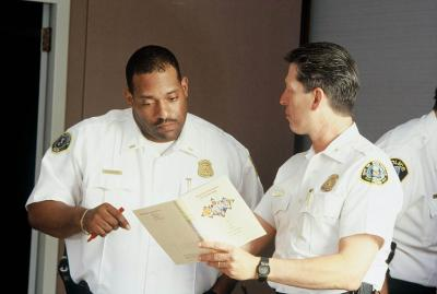 Two police officers looking at a discussion guide