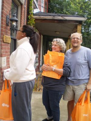 Three volunteers go door to door to distribute welcome bags to new renters.