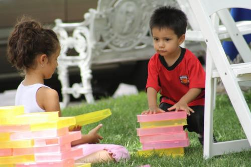 Two young children playing with blocks