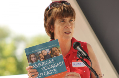 "Woman at a podium holding a document that says ""America's Youngest Outcasts"""