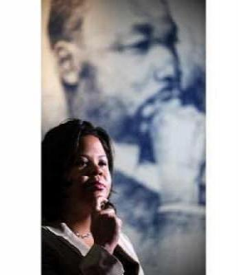 Woman speaking in front of a banner of Martin Luther King, Jr.