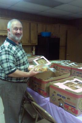 Man standing at table with boxes of food smiling.
